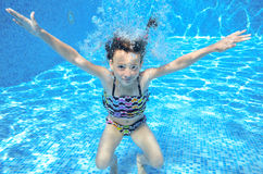 Girl jumps and swims in pool underwater Stock Photography