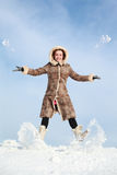 Girl jumps and throw snow hands and feet Royalty Free Stock Photos