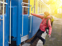 The girl jumps into the train. Stock Photography