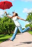 Girl jumps with umbrella Stock Photo