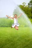 Girl jumps under spray drops Royalty Free Stock Photography