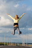 The girl jumps up. Against the sky with the opened hands Stock Image