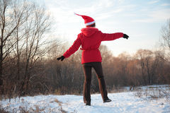 Girl jumps in wood in winter from back Royalty Free Stock Photo