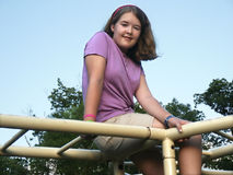 Girl on jungle gym. Girl perched on playground jungle gym Royalty Free Stock Photography