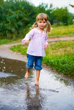 Girl junps barefoot in a puddle royalty free stock photo