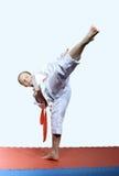 Girl in karategi beats roundhouse kick leg Royalty Free Stock Photography