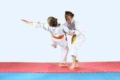 Girl in karategi throws the boy in karategi on the mat Royalty Free Stock Photos