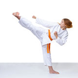 Girl in karategi trains a kick Royalty Free Stock Images
