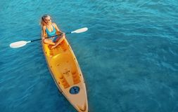 Girl on kayak sea at sunset, healthy lifestyle design. Sport, recreation, adventure outdoors.. stock images