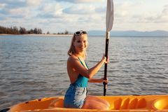 Girl on kayak sea at sunset, healthy lifestyle design. Sport, recreation, adventure outdoors.. royalty free stock photography