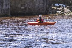 A woman on a mountain river is engaged in rafting. A girl is kayaking down a mountain river.girl in a kayak, side view stock images