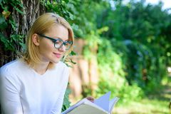 Girl keen on book keep reading. Bestseller top list concept. Woman blonde take break relaxing in park reading book. Girl. Relaxing with book green nature royalty free stock photos