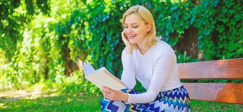 Girl keen on book keep reading. Reading literature as hobby. Girl sit bench relaxing with book, green nature background. Woman blonde take break relaxing in stock photos