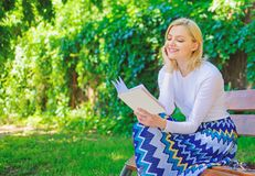 Girl keen on book keep reading. Reading literature as hobby. Woman blonde take break relaxing in park reading book. Girl. Sit bench relaxing with book, green royalty free stock image