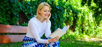 Girl keen on book keep reading. Reading literature as hobby. Girl sit bench relaxing with book, green nature background. Woman blonde take break relaxing in stock image