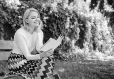 Girl keen on book keep reading. Reading literature as hobby. Woman blonde take break relaxing in park reading book. Girl. Sit bench relaxing with book, green stock image