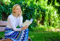 Girl keen on book keep reading. Reading literature as hobby. Woman blonde take break relaxing in park reading book. Girl. Sit bench relaxing with book, green royalty free stock photo