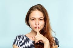 Girl keep secret mystery finger on lips stock images