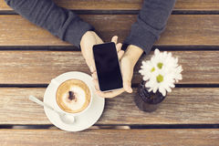 Girl keeping a cell phone and a cup of cappuccino on a wooden ta Royalty Free Stock Photos
