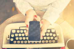 Girl keeping cell phone and a vintage typewriter Royalty Free Stock Images
