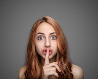 Girl keeping finger on her lips . stock photography