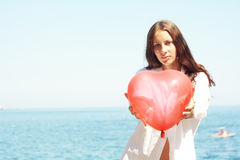 Girl keeps air ball in form heart near sea Stock Photos