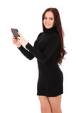 Girl keeps black tablet pc standing sideways. Isolated on white Royalty Free Stock Images