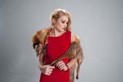 Girl that keeps drooping fur cloak of fox and look. Portrait of a girl that keeps drooping fur cloak of fox and looks aside Royalty Free Stock Photos
