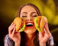 Girl keeps and eating  several hamburger. Happy girl keeps big woman small hamburgers. Fastfood concept on green Stock Images