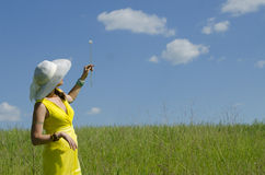 Girl keeps a flower in a hat. The girl keeps a flower in a hat and a yellow dress a dandelion in the blue sky Stock Photo