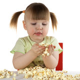 Girl keeps in hand popcorn. Little girl on white background  sits at the table, keeps in hand popcorn and looks at it Royalty Free Stock Image