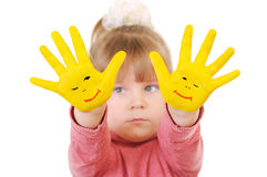 Girl keeps hands painted in yellow Stock Photos