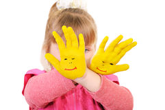 Girl keeps hands painted in yellow Stock Image