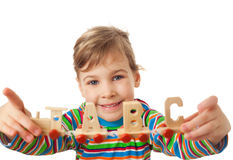 Girl keeps in hands toy wooden steam locomotive. Pretty little girl keeps in hands toy wooden steam locomotive with cars in form of alphabet letters isolated on Stock Images