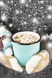 Girl keeps a mug of hot cocoa with marshmallows in mittens Royalty Free Stock Photo