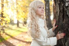 The girl keeps for a tree. The girl in a raincoat keeps for a tree in autumn park Royalty Free Stock Photography