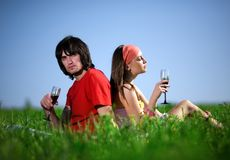 Girl in kerchief and boy with wineglasses on grass Royalty Free Stock Images