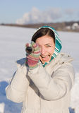Girl in kerchief take a look in spyglass on field. Positive girl in kerchief take a look in spyglass on snowy field Stock Photo