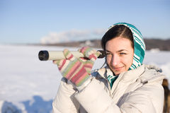Girl in kerchief take a look in spyglass on field. Positive girl in kerchief take a look in spyglass on snowy field Stock Photos