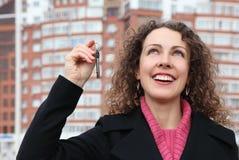 Girl with key looks upwards against many-storeyed Royalty Free Stock Photo