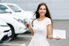 Girl with keys and agreement on background of car dealership. Smilling woman with keys and agreement on background of car dealership Royalty Free Stock Image