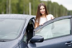 Girl with keys and agreement on background of car dealership Stock Photo
