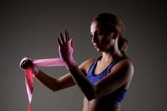 Girl kickboxer. Putting on pink hand wraps Royalty Free Stock Image