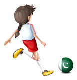 A girl kicking the ball with the flag of Pakistan Royalty Free Stock Photo