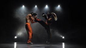 Girl is kicking the guy they are sparring for kickboxing . Light from behind. Smoke background. Girl is kicking the guy they are sparring for kickboxing from the stock footage