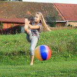 Girl kicking inflating ball Royalty Free Stock Photo