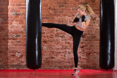 Girl kicking at punching bag Royalty Free Stock Photos