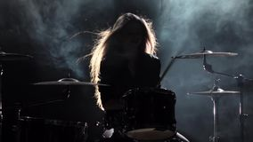 Girl is kicks from playing drums, playing energetic music. Black smoke background. Silhouette. Slow motion stock video