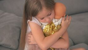 Girl kid cares about a doll, close-up, Girl holding baby doll, dreaming about being adult