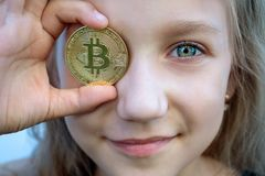 Girl kid with green eyes holding bitcoin digital money. Concept of easy bitcoin investing and trading. stock images